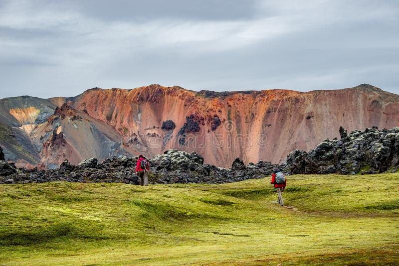 Colorful rainbow rhyolite volcanic mountains Landmannalaugar as pure wilderness in Iceland and hikers, summer time stock images