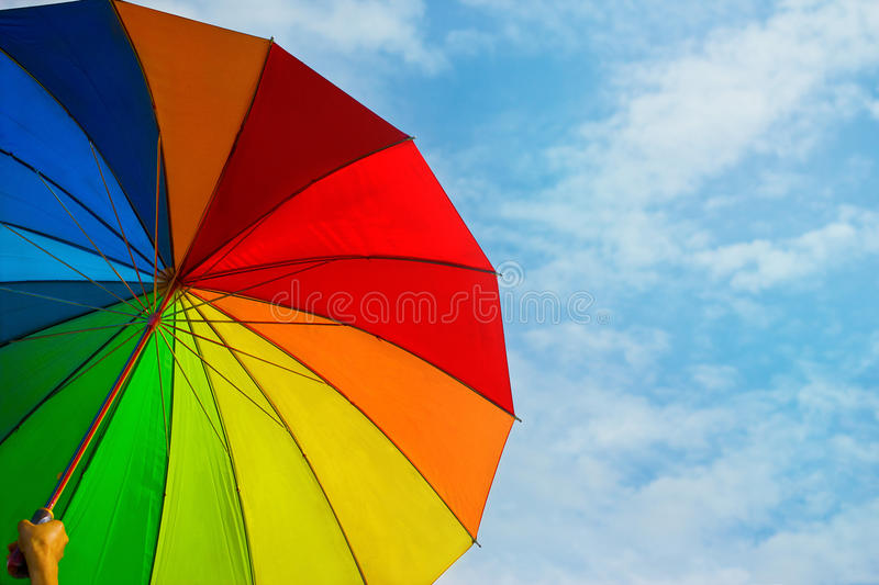 Colorful rainbow umbrella on blue sky background royalty free stock images