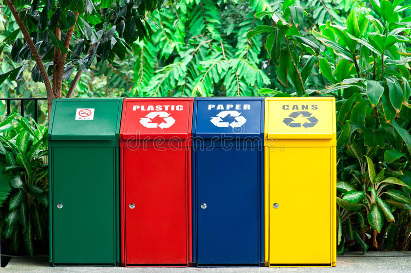 Colorful Recycling Bins. A Row of Colorful Recycling Bin with Plant Background