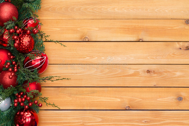 Colorful red Christmas garland border. With tree ornaments and berries in evergreen foliage arranged to the side on cedar wood boards with copy space stock photos