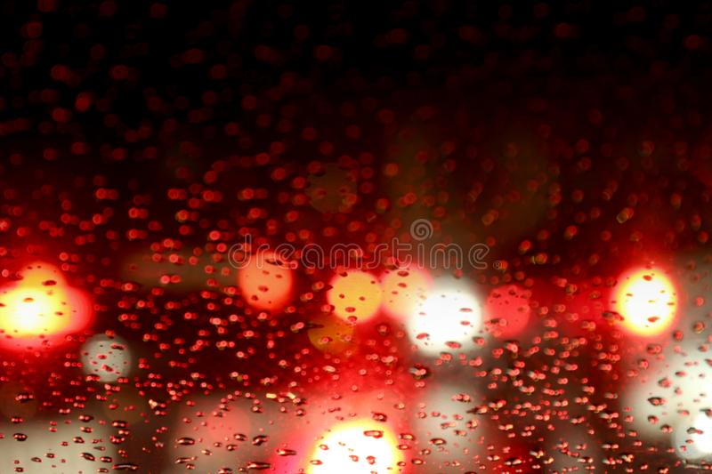 Colorful Red glitter vintage lights bokeh night background, Defocused bokeh dot glitter light on Rainy night background royalty free stock photography