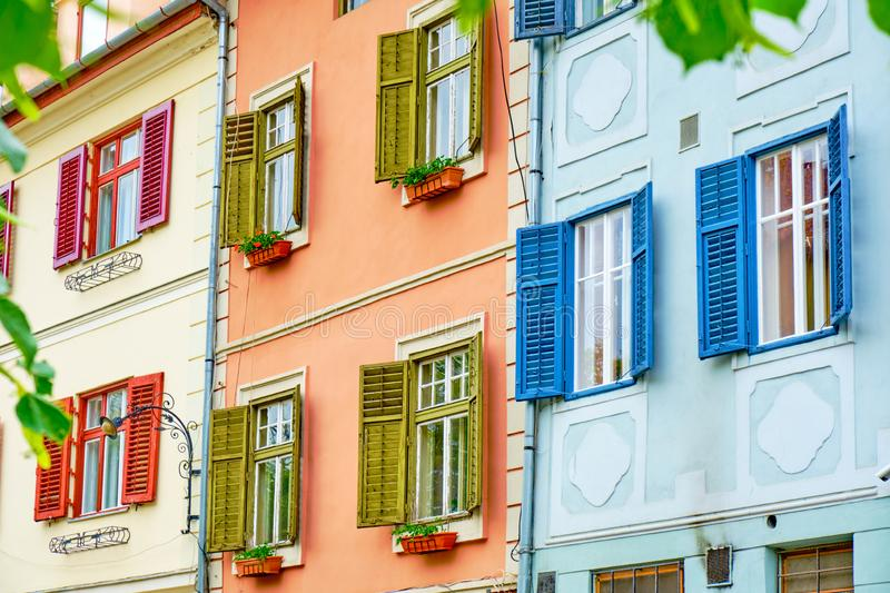 Colorful red, green, and blue wooden shutters on white windows, in bright day. Three buildings side by side in Sibiu, Romania.  stock photography