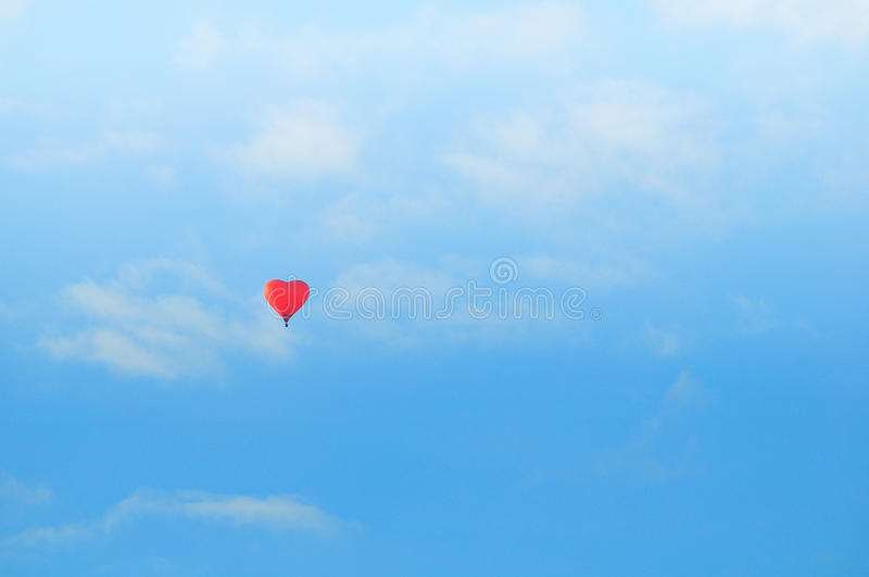 Colorful red heart shaped balloon flying in the blue sunny sky. Pastel correction. royalty free stock photos