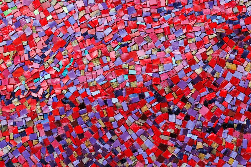 Colorful red, pink, yellow, and purple stone mosaic tiles on the wall royalty free stock photos