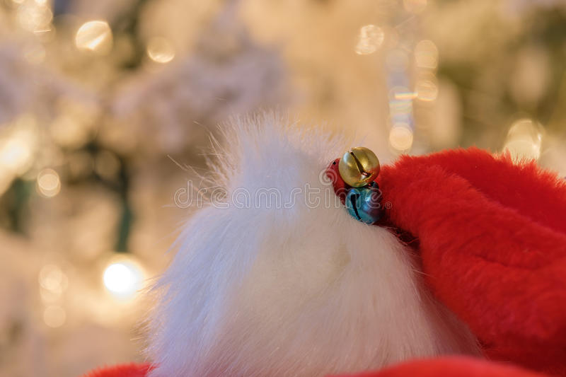 Colorful red Santa hats with blue and gold bells against a snow royalty free stock photo