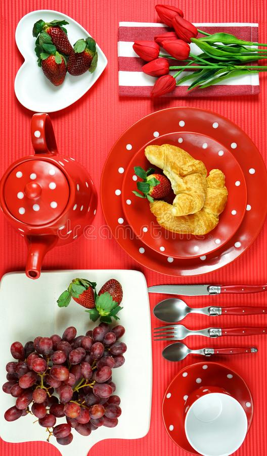 Colorful red theme breakfast brunch table setting flatlay. Modern bright colorful red theme morning breakfast or brunch table setting, flat lay royalty free stock photo