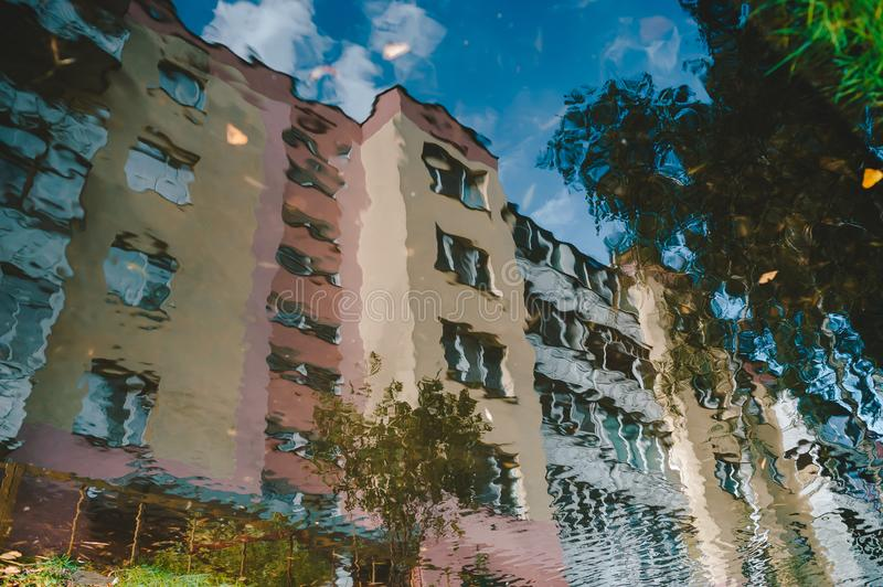 Colorful reflection in a puddle of a high-rise residential building royalty free stock photography
