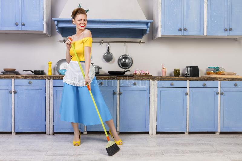 Retro pin up girl housewife in the kitchen. Colorful retro / pin up girl woman female adult / housewife wearing colorful top, skirt and white apron holding mop royalty free stock photo