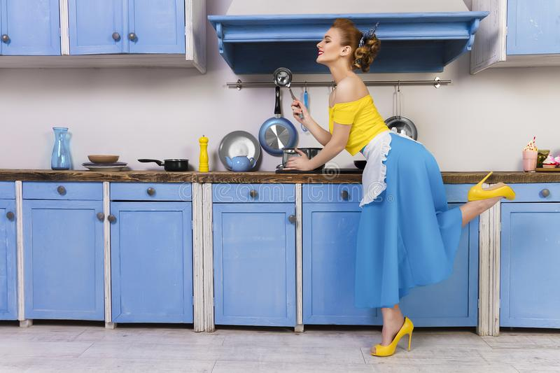 Retro pin up girl housewife in the kitchen. Colorful retro / pin up girl woman female / housewife wearing colorful top, skirt and white apron holding ladle and stock photo