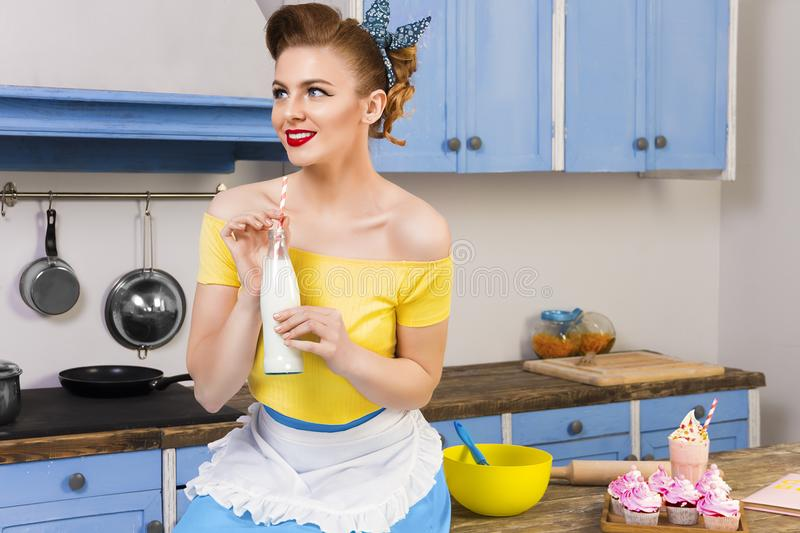 Retro pin up girl housewife in the kitchen royalty free stock photo