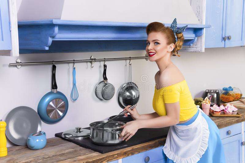 Retro pin up girl housewife in the kitchen royalty free stock image