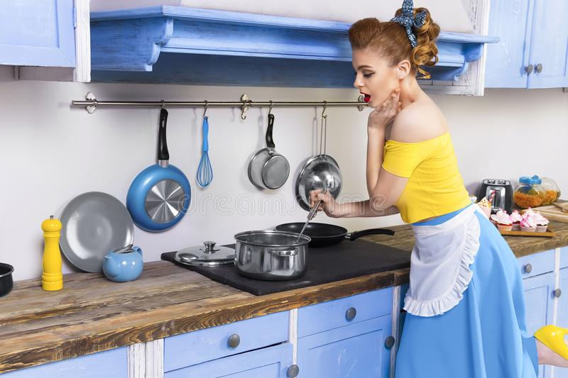 Retro pin up girl housewife in the kitchen stock images