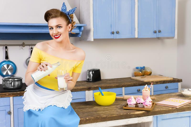Retro pin up girl housewife in the kitchen. Colorful retro / pin up girl woman female / housewife wearing colorful top, skirt and white apron sitting in the stock image