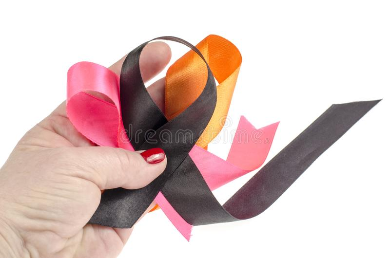 Colorful ribbons on hand, cancer awareness. Studio Photo stock photos