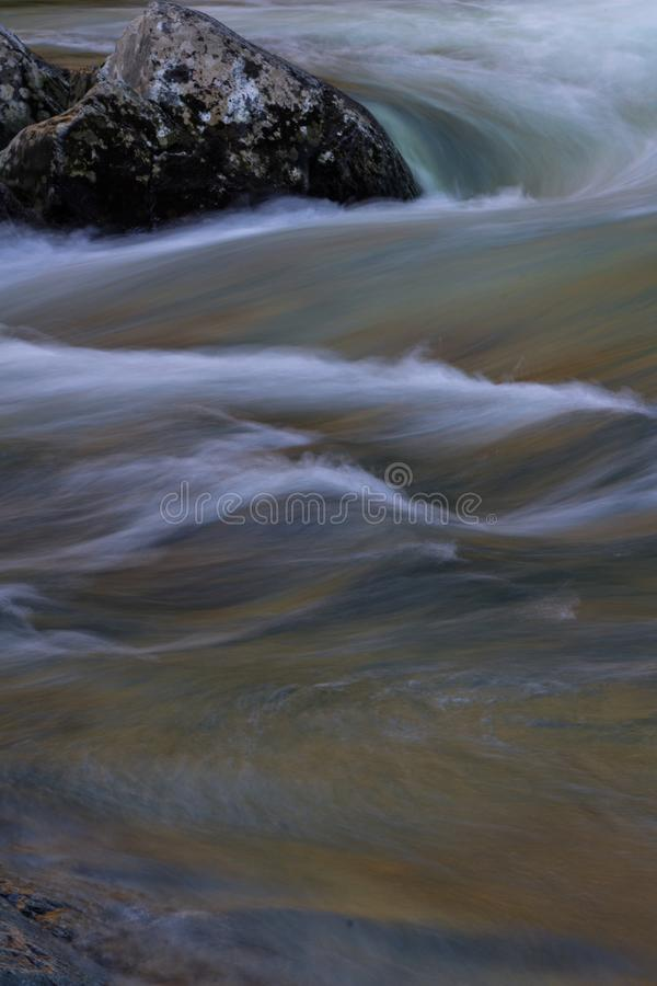 Colorful river water currents swirling around a rock, space for text. Vertical aspect stock image