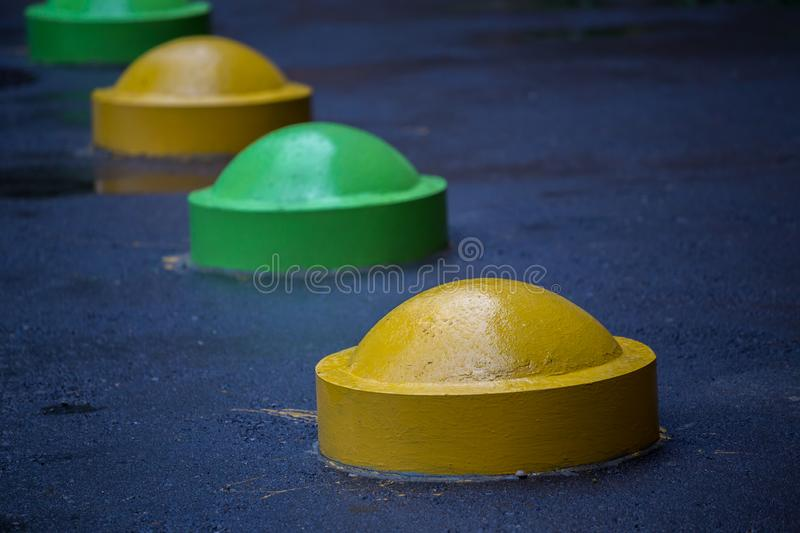 Colorful road parking prevention hemisphere bollards close-up with selective focus and blur royalty free stock photos