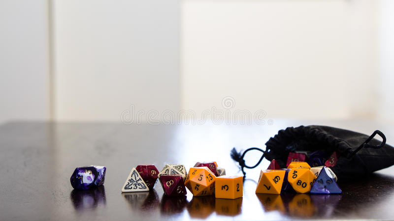 Colorful roleplaying dice scattered on a table with reflection royalty free stock photography