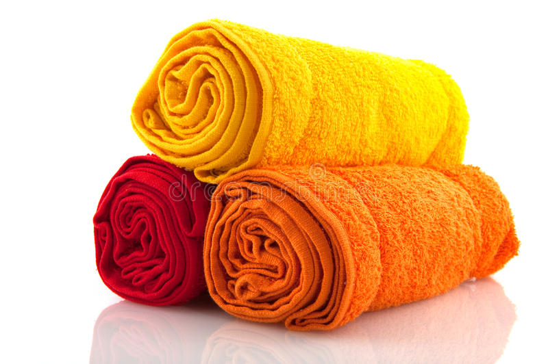 Colorful rolled towels. In yellow red and orange royalty free stock photos