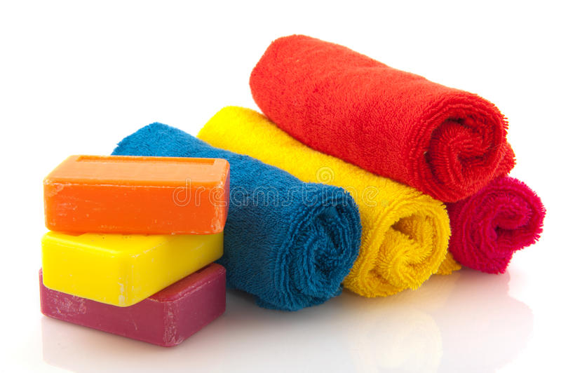 Colorful rolled towels with soap. Colorful rolled towels with bars soap isolated over white stock image