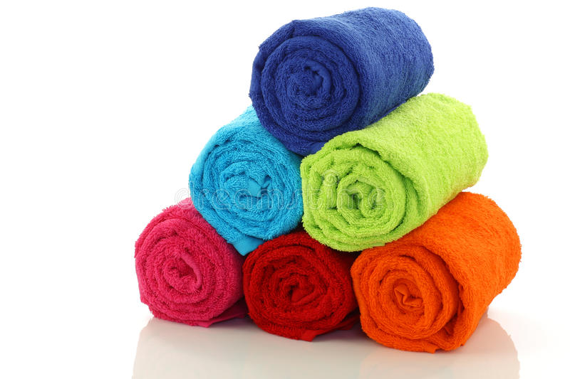 Colorful rolled up and stacked bathroom towels. On a white background stock image