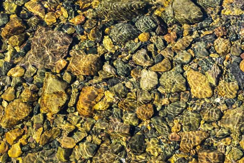 Colorful rolling stones pattern with still water. Colorful sea stones under still water. Iridescent sunlight on the stones. Transp. Arent clear water of sea royalty free stock photo