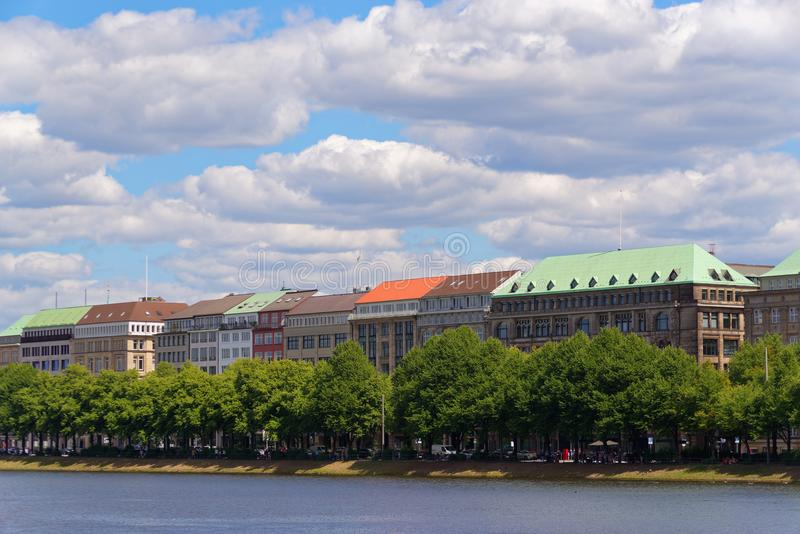 Colorful roofs of buildings on Ballindamm, Jungfernstieg against blue cloudy sky stock image