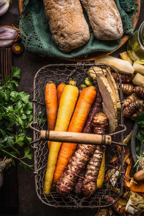 Colorful root vegetables in harvest basket on dark wooden kitchen table background, top view. Healthy and clean food and eating royalty free stock photo