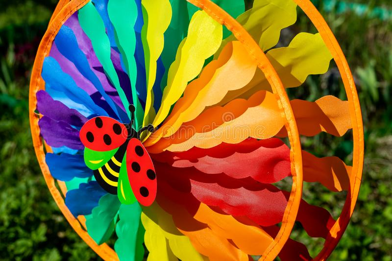 A colorful rotating toy pinwheel with a head of butterfly.Holiday background,windmill toy mill.Rainbow pinwheel outdoor stock image