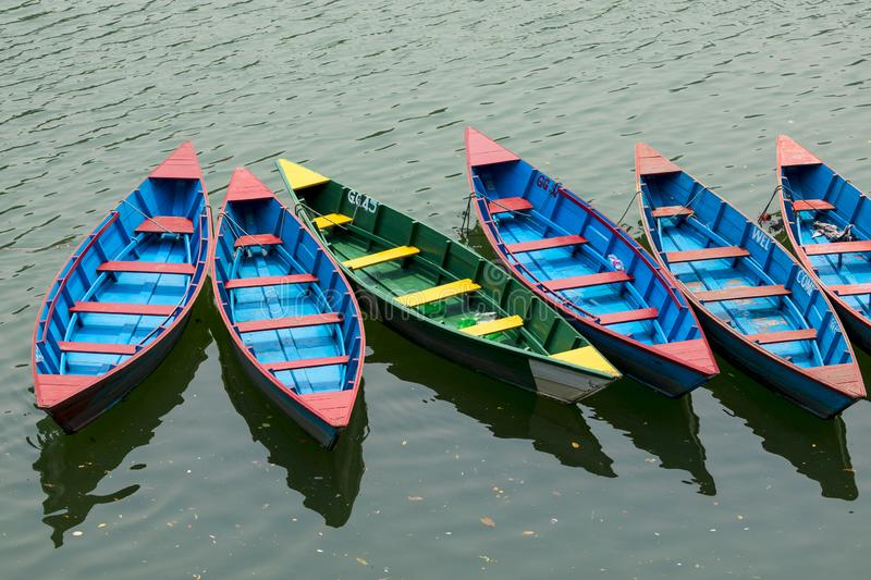 Colorful row boats docked on Lake Phewa in Pokhara. Nepal royalty free stock photo