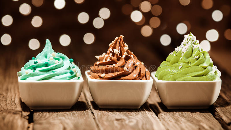 Colorful row of frozen yogurt desserts at a party. Colorful row of three different frozen yogurt desserts in blue, brown and green garnished with nuts and sugar royalty free stock photography