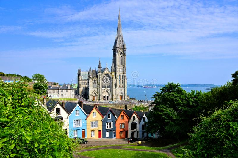 Colorful row houses with cathedral in background, Cobh, County Cork, Ireland. Colorful row houses with towering cathedral in background in the port town of Cobh royalty free stock photography
