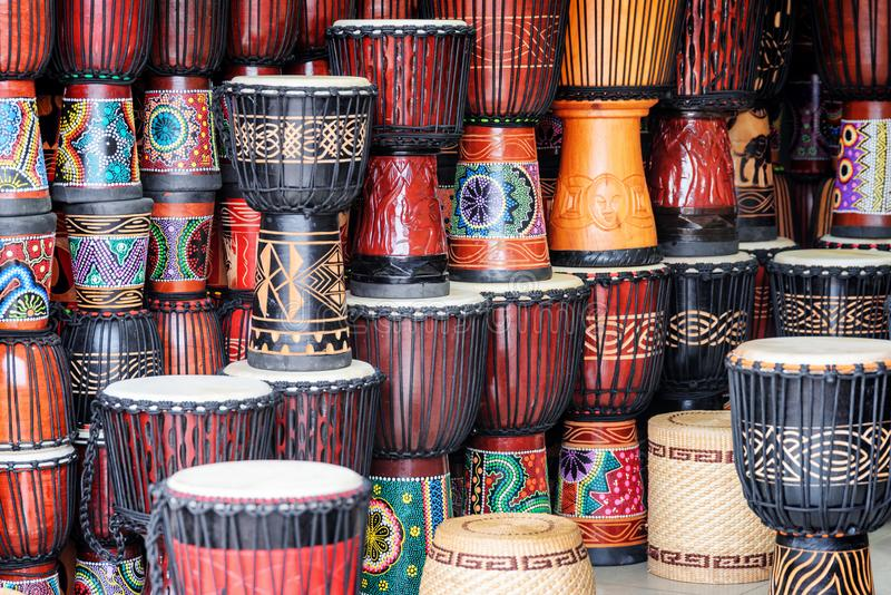 Colorful rows of wooden djembe drums at souvenir shop. Fenghuang, China - September 22, 2017: Colorful rows of wooden djembe drums at souvenir shop in Phoenix stock images