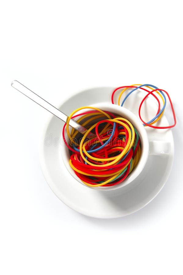 Colorful rubber bands in breakfast cup. Abstract metaphor of colorful rubber bands in breakfast cup royalty free stock image