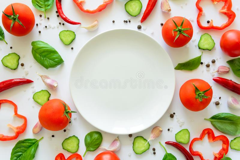 Colorful salad ingredients pattern made of tomatoes, pepper, chili, garlic, cucumber slices, basil and empty plate on white backgr royalty free stock photos