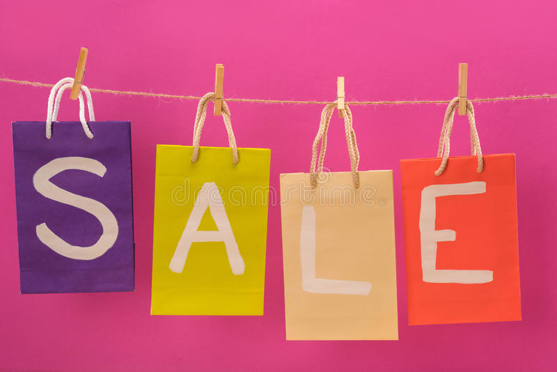 Colorful sale signs on shopping bags hanging on rope isolated on pink. Offer sale tags stock photography