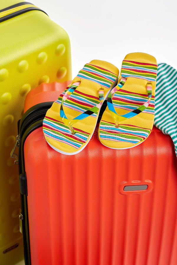 Colorful sandals on red suitcases. Clothes and wheeled suitcases, cropped image royalty free stock photo