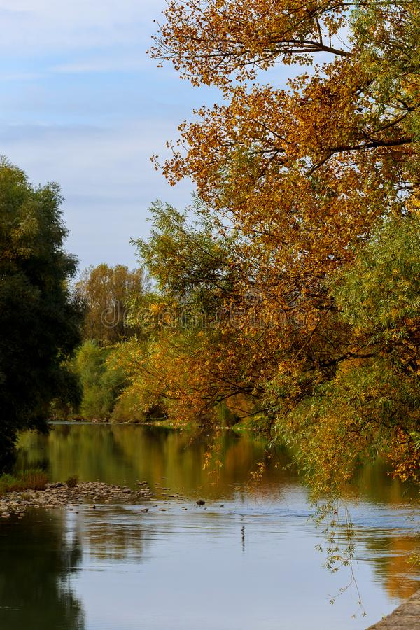 Colorful scenic idyllic autumn landscape at a river shore with trees reflecting on the water on a sunny autumn day stock photography