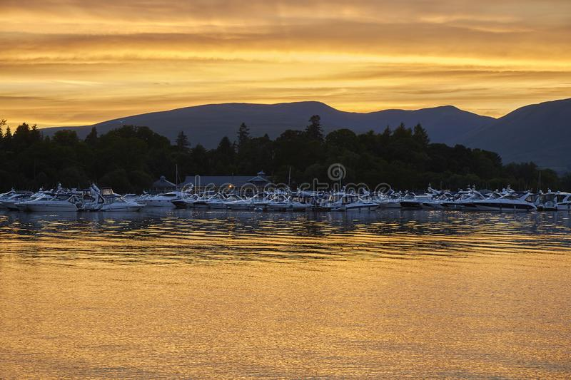Colorful scenic sunset view of boats floating on Loch lomond lake in Scotland, United Kingdom. royalty free stock image