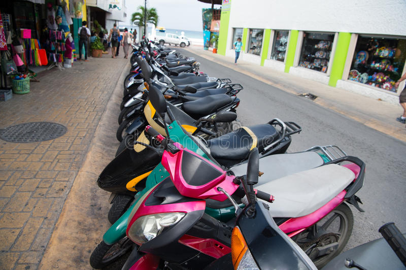 Colorful scooters or motorcycles for sale or hire, Cozumel, Mexico. Colorful scooters or motorcycles for sale or hire standing in row with wheels and lights on stock photography