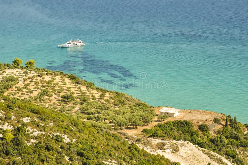 Colorful seascape of blue sea, green coast and white boat. royalty free stock photography