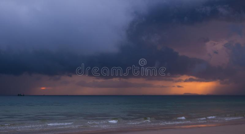 Colorful seascape with thunderclouds and lonely small boat scurrying to the shining island in skyline. royalty free stock image