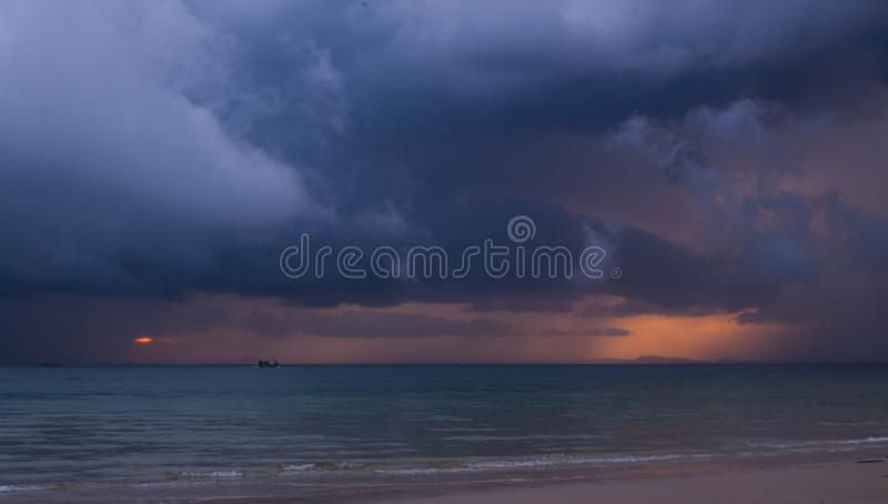 Colorful seascape with thunderclouds and lonely small boat scurrying to the shining island in skyline. royalty free stock images