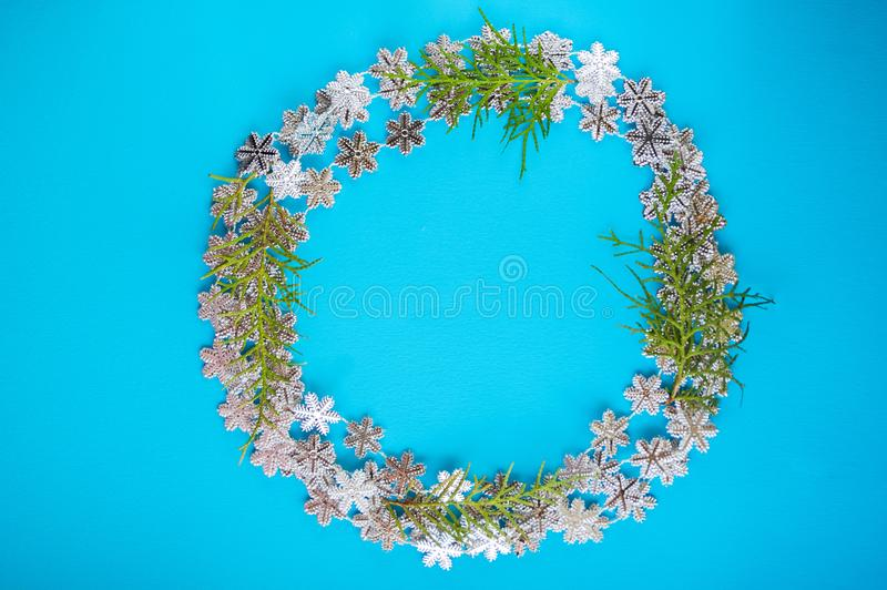 Colorful seasonal pattern of snowflakes, Christmas tree branches on a blue background in the shape of a Christmas wreath. Winter h stock photography