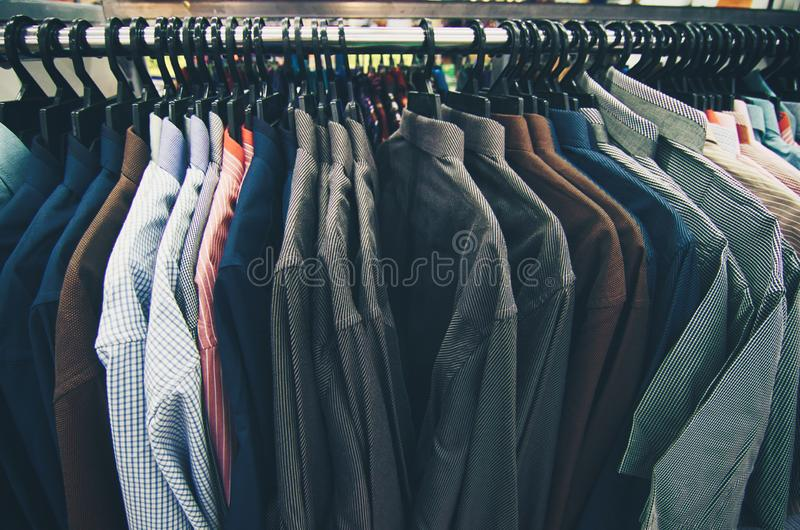 Selection of clothes for men hanging on hangers in shopping mall for store sale concept royalty free stock photos