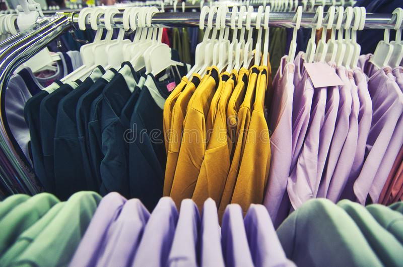 Selection of clothes for women hanging on hangers in shopping mall royalty free stock photography