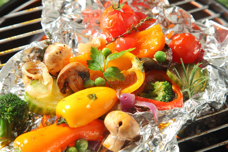 Colorful selection of fresh roasted vegetables. Grilling over a barbecue fire on aluminum foil for a healthy vegetarian or vegan picnic or as an accompaniment stock images