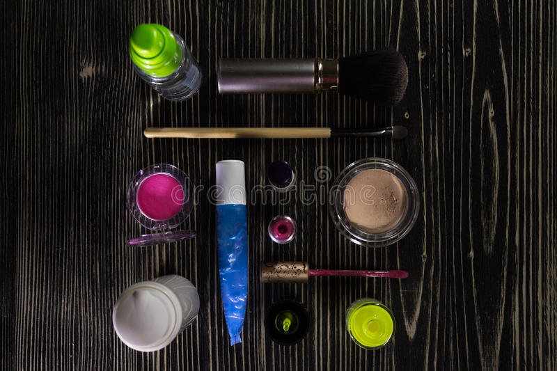Colorful set of makeup products - foundation, lip gloss, blush, eyeshadow, concealer, face cream, primer, brush, nail polish on na royalty free stock images
