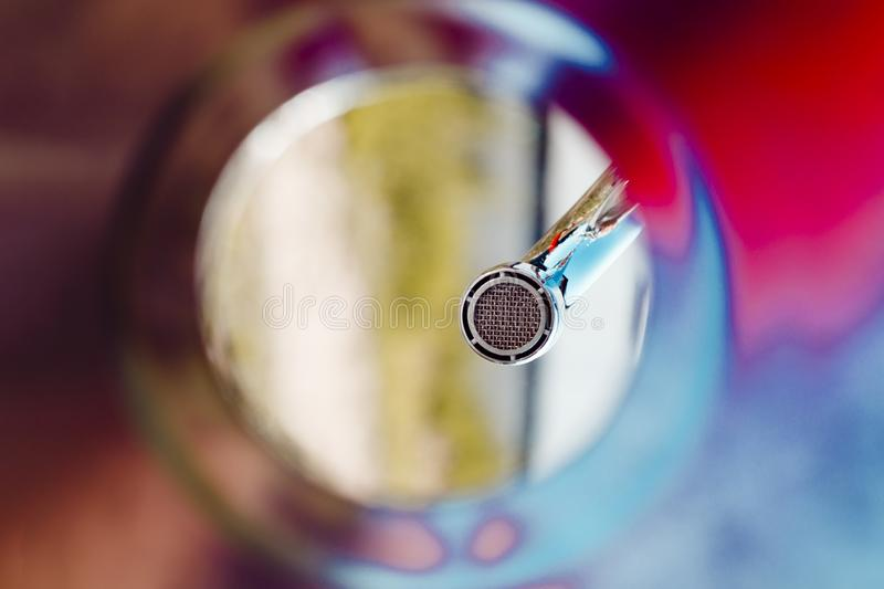 colorful shell, bottom view. faucet aerator, close up. green wood background royalty free stock photography