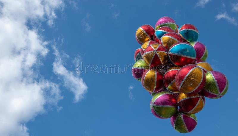 Colorful shiny balloons with white stripes and colored areas in front of an almost cloudless blue sky. Fun royalty free stock photo