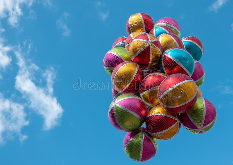 Colorful shiny balloons with white stripes and colored areas in front of an almost cloudless blue sky. Fun royalty free stock photos